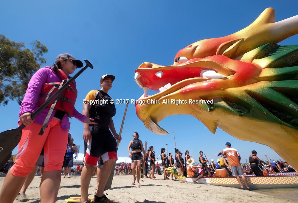 新华社照片,洛杉矶,2017年7月31日<br />     (国际)(2)第二十一届加州长滩龙舟节<br />     7月30日,参赛选手上船准备竞争。<br />     在美国洛杉矶长滩市海滨体育场举行的第二十一届年度长滩龙舟节,吸引百余队上千选手参赛。长滩龙舟节是加州最大的龙舟比赛,同时也展示了中国古代龙舟赛的运动。<br />     新华社发(赵汉荣摄)<br /> Dragon Boat racers load their boat in preparation to compete a 500-meter race at the 21st Annual Long Beach Dragon Boat Festival at Marine Stadium in Long Beach, California, the United States, on July 30, 2017. The Long Beach Dragon Boat Festival is held every year in July at Marine Stadium to hosting the largest dragon boat competitions in California. It showcases the ancient Chinese sport of dragon boat racing. (Xinhua/Zhao Hanrong)(Photo by Ringo Chiu)<br /> <br /> Usage Notes: This content is intended for editorial use only. For other uses, additional clearances may be required.