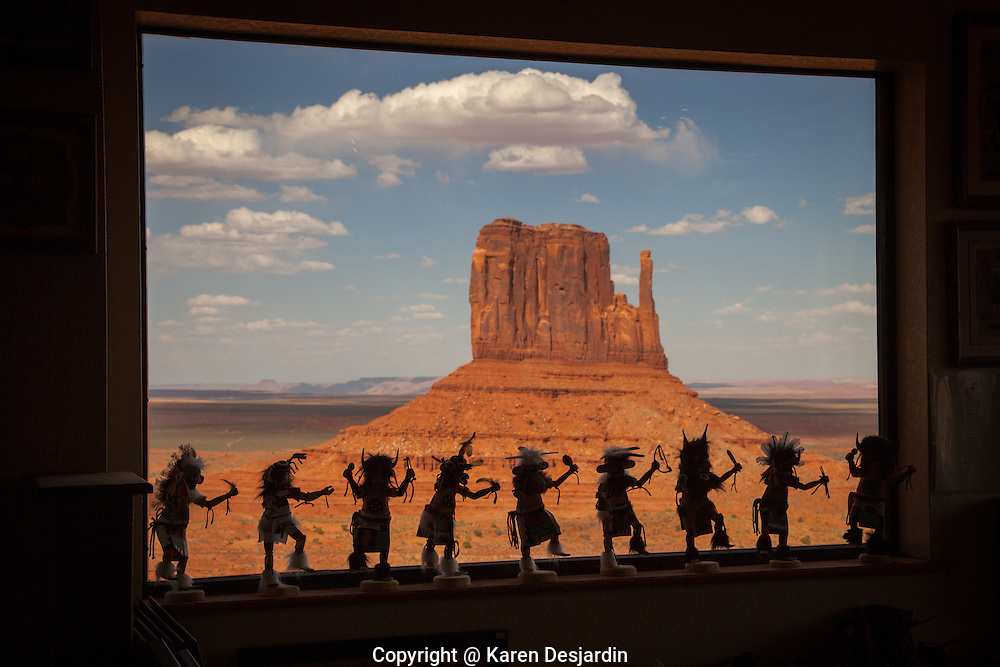 Silhouettes of Kachina dolls for sale in a tourist gift shop our outlined in a window with view of West Mitten butte in Monument Valley, Arizona