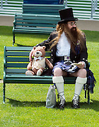 © Licensed to London News Pictures. 17/06/2014. Ascot, UK. A man sits on a bench holding a stuffed toy.  Day one at Royal Ascot 17th June 2014. Royal Ascot has established itself as a national institution and the centrepiece of the British social calendar as well as being a stage for the best racehorses in the world. Photo credit : Stephen Simpson/LNP