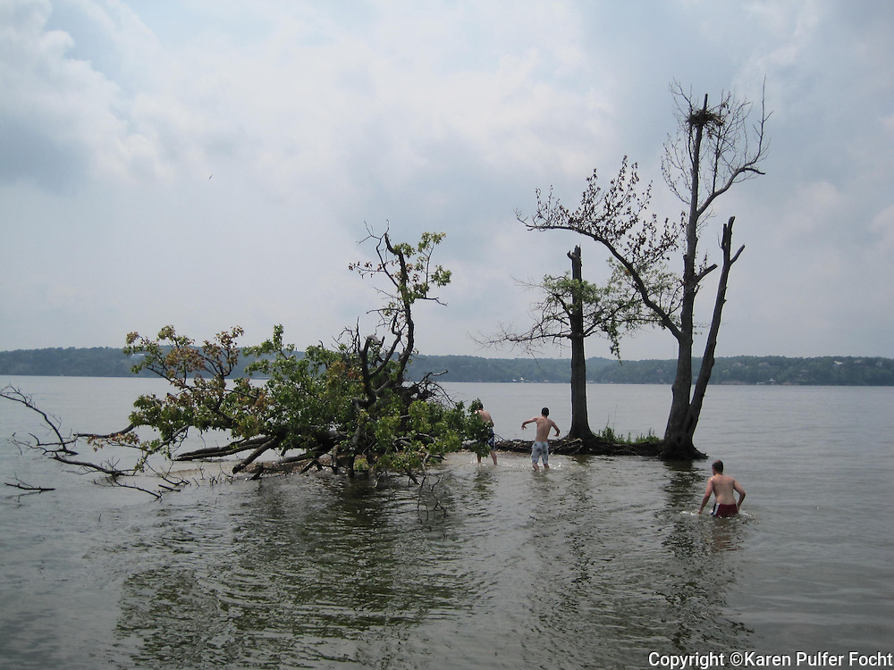 Young boys enjoy playing on an island in The Tennessee River at Pickwick Lake, in Tennessee.