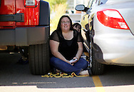 "Amber Makham sits in the shade between two cars in line for casting for season 11 of ""The Biggest Loser"" television show in Broomfield, Colorado July 17, 2010.  Over 600 people waited in sweltering heat for a chance to be on the show and win $250,000.   REUTERS/Rick Wilking (UNITED STATES)"