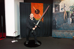 © Licensed to London News Pictures. 09/02/2015. London, UK. A visitor to the Game of Thrones exhbition poses with a sword on 9th February 2014 at the O2 Arena in Greenwich, south-east London. Photo credit : Vickie Flores/LNP