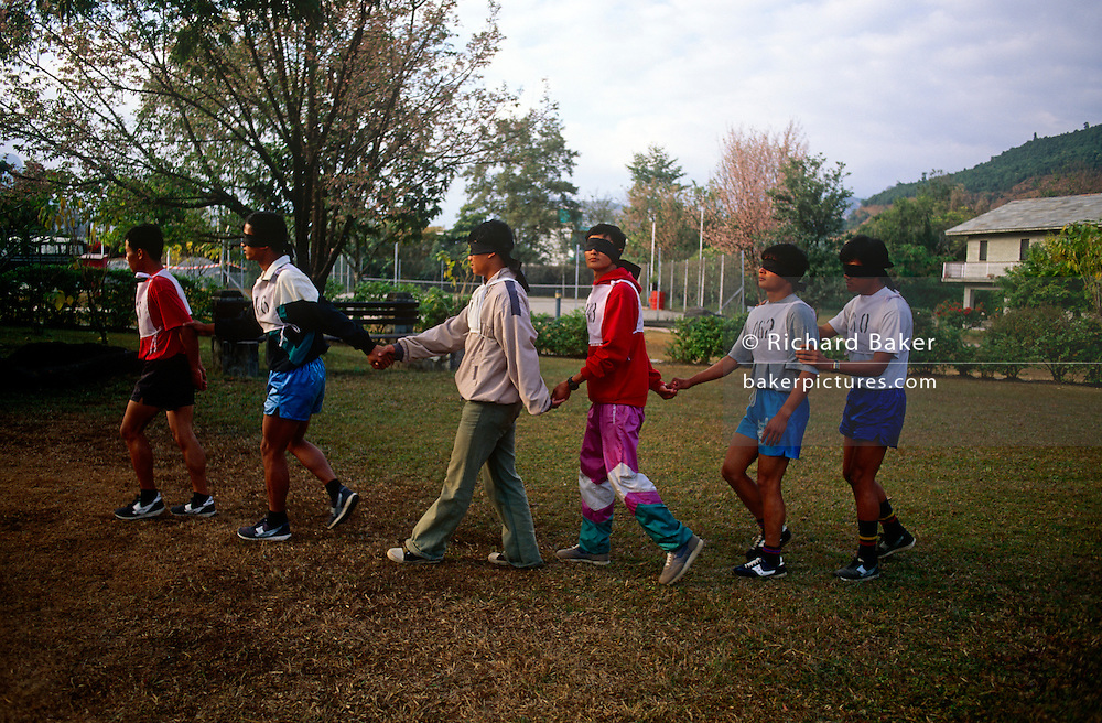 Young Nepali boys do a leadership initiative test in Pokhara  camp, hoping to be recruited for the Gurkha Regiment in the British army. This is part of a tough endurance series to find physically perfect specimens for British army infantry training. For example, they will need to perform 25 straight-kneed sit-ups at a 45° slant both within 60 seconds to pass. 60,000 boys aged between 17-22 (or 25 for those educated enough to become clerks or communications specialists) report to designated recruiting stations in the hills each November, most living from altitudes ranging from 4,000-12,000 feet. After initial selection, 7,000 are accepted for further tests from which 700 are sent down here to Pokhara in the shadow of the Himalayas. Only 160 of the best boys succeed in the journey to the UK. The Gurkhas have been supplying youth for the British army since the Indian Mutiny of 1857.