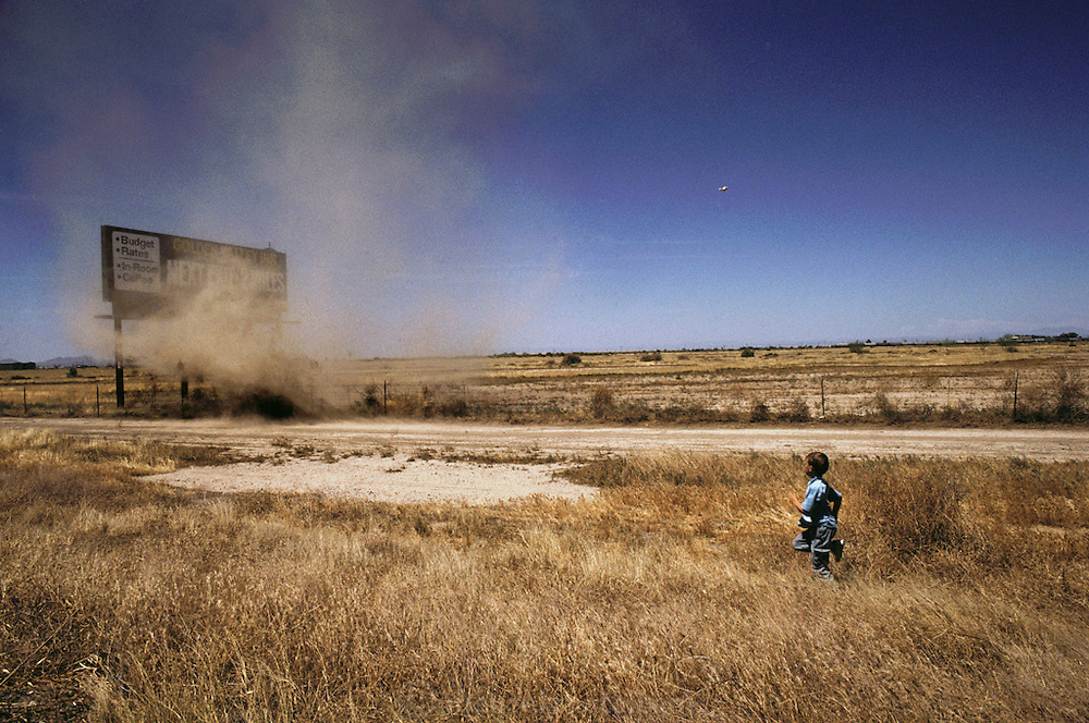 Weather: Evan Menzel, 6, runs toward a dust devil, a small whirlwind, near Casa Grande, Arizona.  Dust devils usually last for a short period of time but can swirl dust and debris to great heights. Desert. Model Released (1991)