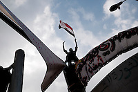 An Egyptian man stands atop a pole in Tahrir Square during Day 16 of 18 days of demonstrations that would lead to the resignation of Hosni Mubarak. (Cairo, Egypt - February 9, 2011)