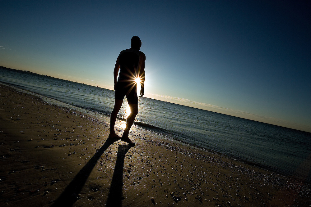 A triathlete prepares to take to the water while he trains in the early morning sun at Lighthouse Beach, Sanibel, FL.