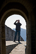Tourist takes a photograph on the ancient Great Wall of China at Mutianyu, north of Beijing