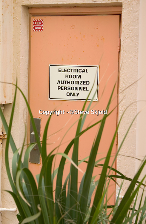 Juxtaposition of beach plants and electrical room door.  North Redington Beach Tampa Bay Area Florida USA