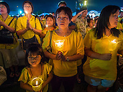 05 DECEMBER 2014 - BANGKOK, THAILAND: Thais hold lit candles aloft for the King's Birthday on Sanam Luang in Bangkok. Thais marked the 87th birthday of Bhumibol Adulyadej, the King of Thailand,  Friday. The King was born on December 5, 1927, in Cambridge, Massachusetts. The family was in the United States because his father, Prince Mahidol, was studying Public Health at Harvard University. He has reigned since 1946 and is the world's currently reigning longest serving monarch and the longest serving monarch in Thai history. Bhumibol, who is in poor health, is revered by the Thai people. His birthday is a national holiday and is also celebrated as Father's Day. He is currently hospitalized in Siriraj Hospital, recovering from a series of health setbacks.     PHOTO BY JACK KURTZ