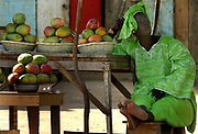 A Senegalese woman relaxes on a wooden chair whilst selling Mango's on the roadside in Norflaye Senegal, Sunday 16 May 2004. The Mango is a common fruit found in Senegal at this time of year. A bowl of 10 ripe Mangos sells for less than 2 Euros.<br /> EPA PHOTO/NIC BOTHMA