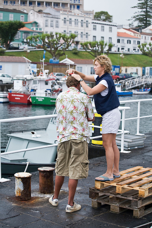 a crew member gets a haircut on the dock in the harbor of Horta on the island of Faial. One of of the Azores,  a group of islands in the Atlantic that are a part of Portugal and the European Union.
