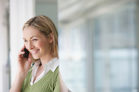 Business woman using mobile phone in office portrait