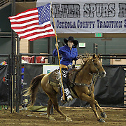 A cowgirl rides with the American flag during the beginning of the 129th performance of the PRCA Silver Spurs Rodeo at the Silver Spurs Arena   on Friday, June 1, 2012 in Kissimmee, Florida. (AP Photo/Alex Menendez) Silver Spurs rodeo action in Kissimee, Florida. PRCA rodeo event in Florida. The 129th annual running of the cowboy event.