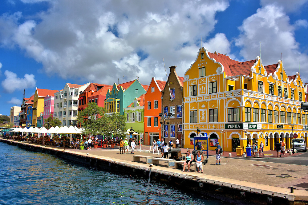 Rainbow of Colorful Buildings in Punda, Eastside of Willemstad, Curaçao <br /> The beautiful hallmark of Willemstad is Dutch architecture in a kaleidoscope of colors like these along Handelskade. This charming characteristic dates back to 1816 when Governor Albert Kikkert blamed his migraine headaches on the sun reflecting off the white buildings. He issued a degree demanding everything be painted any color but white. Within three years the town became a rainbow. After he died in 1819, it was learned Kikkert owned a majority share of the only local paint company.