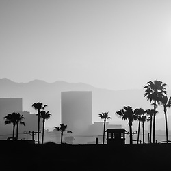 Newport Beach skyline sunrise panorama photo in black and white. Panoramic photo ratio is 1:3 and includes Newport Beach office buildings in Fashion Island, palm trees, and mountains overlooking Orange County in Southern California.