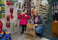 Raina Welch helps Bethany Stockman fill up a bag showing just how much merchandise you can fit for their upcoming Black Friday 20% off sale.  (Karen Bobotas/for the Laconia Daily Sun)