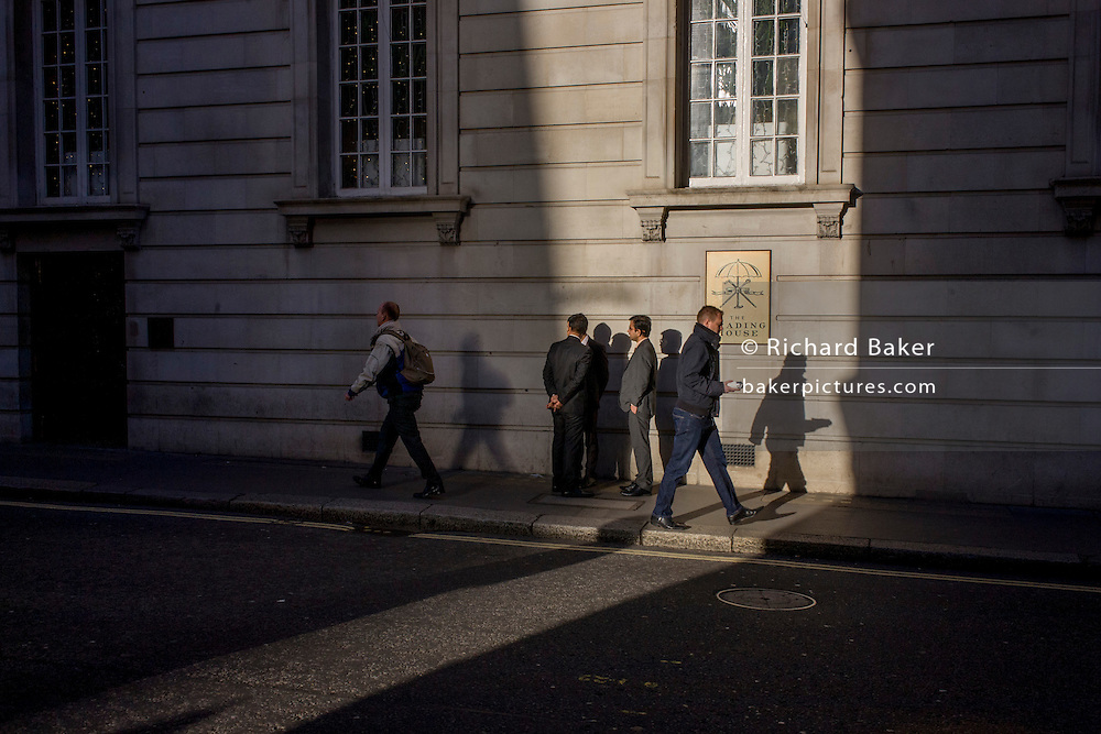 Businessmen in walk through winter sunlight in the City of London.