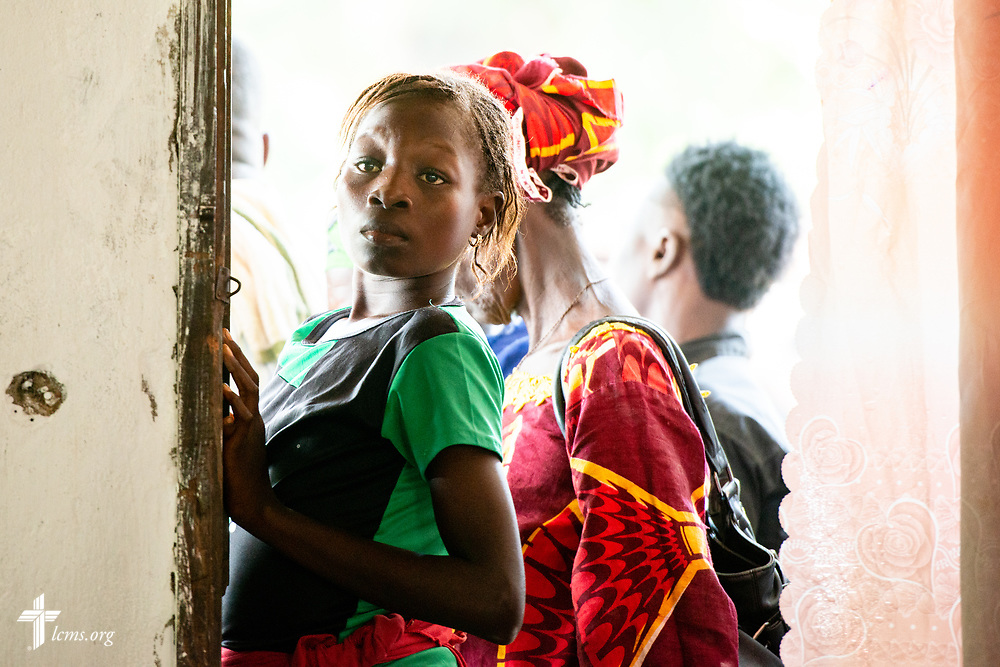 A young woman waits for treatment on the first day of the LCMS Mercy Medical Team on Monday, May 7, 2018, in the Yardu village outside Koidu, Sierra Leone, West Africa. LCMS Communications/Erik M. Lunsford