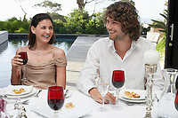 Friends sitting outside near pool socialising at Dinner Party
