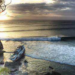 An abandon taiwanese fishing boat founders on a reef near one of Bali's finest surf breaks.