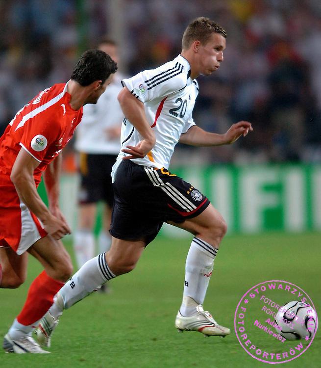 n/z.: Michal Zewlakow (nr14-Polska) , Lukas Podolski (nr20-Niemcy) podczas meczu grupy A Polska (czerwone) - Niemcy 0:1 podczas turnieju finalowego Mistrzostw Swiata Niemcy 2006 , pilka nozna , Niemcy , Dortmund , 14-06-2006 , fot.: Adam Nurkiewicz / mediasport..Michal Zewlakow (nr14-Poland) and Lukas Podolski (nr20-Germany) fight for the ball during soccer match group A in Dortmund during World Cup 2006. June 14, 2006 ; Poland (red) - Germany 0:1 ; football , Germany , Dortmund ( Photo by Adam Nurkiewicz / mediasport )
