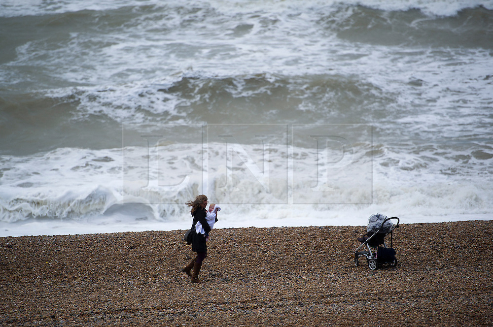 © London News Pictures. 25/09/2012. Brighton, UK.  A moan braving heavy winds with her baby on Brighton beech  on September 25, 2012. Photo credit : Ben Cawthra/LNP.