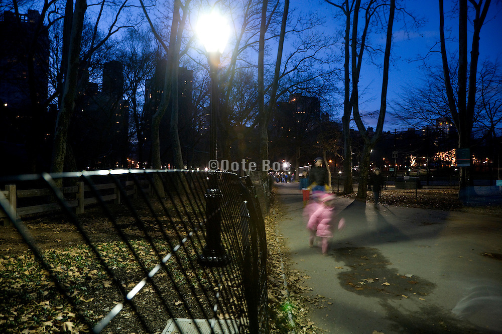 Central park in New York City at dusk with people walking