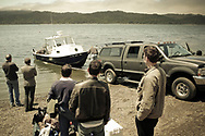 Five men watch as a boat is pulled out of Tomales Bay near Marshall, California. Point Reyes National Seashore is visible in the distance.
