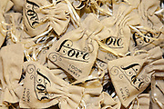 Small burlap wedding favor bags with a ribbon drawstring that read Love 100% sweet, perfect for  a rustic wedding