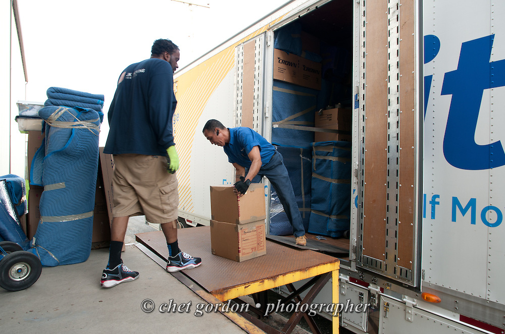 Over the road driver Jose Williams (right) unloads cartons from his trailer at a warehouse in Harrisburg, PA on Monday May 4, 2015. Williams, a cross country trucker with a national household moving company, made the first of two delivery stops on the East Coast with loads that originated in California's Bay Area the week of April 27th.  © Chet Gordon/THE IMAGE WORKS