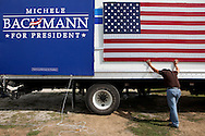 A staff member holds up a flag during preparations for a campaign stop by Republican presidential hopeful Michele Bachmann on Tuesday, August 9, 2011 in Humboldt, IA.