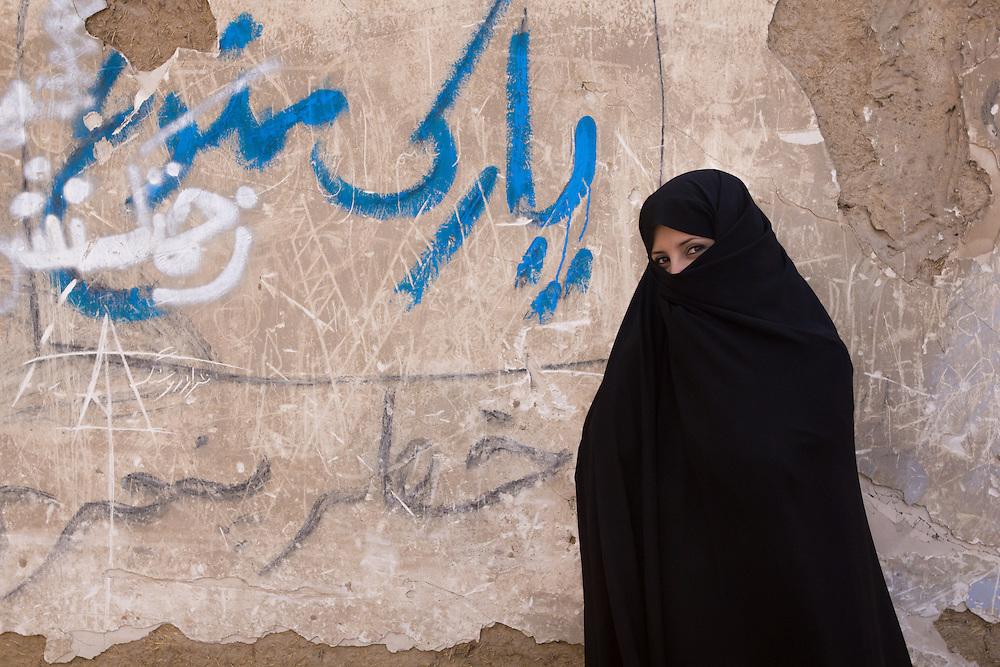 Young muslim woman, wearing a traditional Persian black chador, in Yazd, Iran.