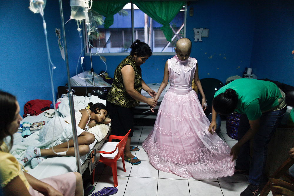 In this photo taken on Thursday, Aug. 25, 2011. A leukemia patient Maria Jose Martinez, fourteen  years old fits her 'Quinceanera' dress at her hospital room 'La Mascota' Managua, Nicaragua. Maria Jose was admitted for her Treatment at La Mascota Hospital in May. 10 of 2011 until August. 29 of 2011, during that period she stayed one month at the intensive care unit. The Association of Parents of children with leukemia and Cancer in Nicaragua, Mapanica, have been organizing for their third year the 15 year old celebration of young girls that have been struggling with the cancer and they still are battling to win this fight against some type of cancer and leukemia at the Childrens hospital La Mascota, in Managua, Nicaragua.