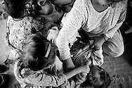 Hamida plays with her children and tickles Ahmed Ali. Karachi, Pakistan, 2010