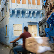 Boy riding bicycle through blue painted laneway of Jodhpur