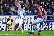 Alex Pritchard of Huddersfield Town (21) controls the ball under pressure from Fabián Balbuena of West Ham United (4) during the Premier League match between Huddersfield Town and West Ham United at the John Smiths Stadium, Huddersfield, England on 10 November 2018.