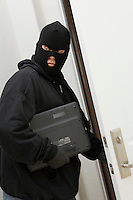 Burglar stealing laptop