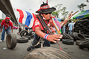 May 2 - BANGKOK, THAILAND: A Red Shirt protestor wearing a Thai flag helps bring tires to the new Red Shirt barricades in Bangkok Sunday. The Red Shirts moved  their barricades in the Sala Daeng Intersection in Bangkok Sunday further away from King Chulalongkorn Memorial Hospital after a threat that the government would move them out if they didn't move themselves. The move gave people full access to the hospital. The stand off between the Red Shirts and the government enters its third month in May. The Red Shirts continue to call for Thai Prime Minister Abhisit Vejjajiva to step down and dissolve parliament and demand the return of ousted Prime Minister Thaksin Shinawatra.   PHOTO BY JACK KURTZ