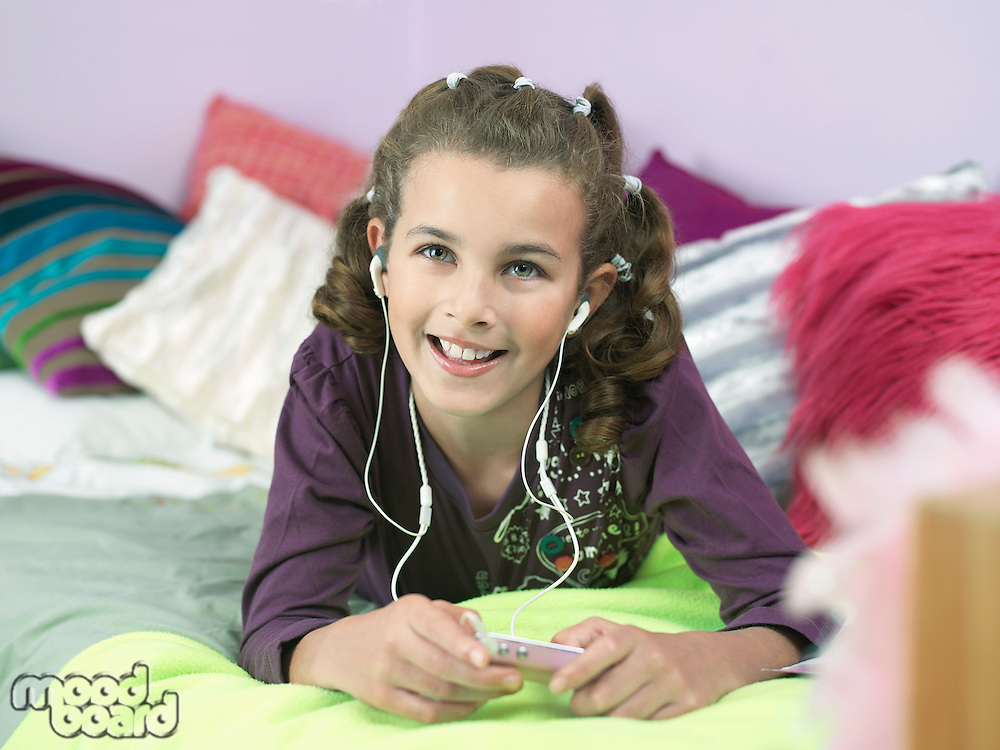 Young Girl lying on front Listening to MP3 Player on bed
