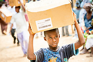 A boy walks medication delivered to the clinic site on the first day of the LCMS Mercy Medical Team on Monday, May 7, 2018, in the Yardu village outside Koidu, Sierra Leone, West Africa. LCMS Communications/Erik M. Lunsford