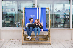 © Licensed to London News Pictures. 31/03/2018. Brighton, UK. A couple take a break in a giant deck chair outside the Brighton i360 tower during the Easter Bank Holiday weekend. Photo credit: Hugo Michiels/LNP