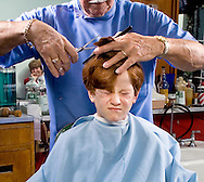 Young boy not liking getting a haircut.