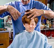 Young boy not enjoying his haircut.