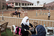 Aya Alajrami 17 anni doing her homework on her laptop before her horse back riding lesson.
