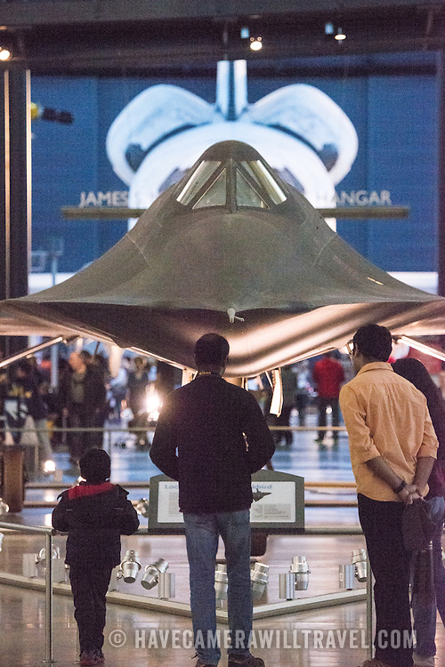 Visitors stand in front of the Lockheed SR-71 Blackbird on display at the Smithsonian National Air and Space Museum's Udvar-Hazy Center. Located near Dulles Airport, the Udvar-Hazy Center is the second public facility of the Smithsonian's National Air and Space Museum. Housed in a large hangar are a multitude of planes, helicopter, rockets, and space vehicles. In the background are the bulging rocket thrusters of the Space Shuttle Discovery. Please note that due to the low light conditions that this was shot in, it contains some image noise when viewed at large resolutions.