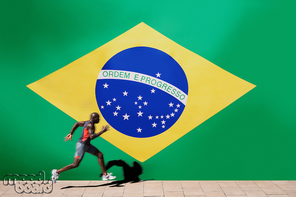 Athlete running past Brazilian flag