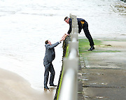 UKIP 2015 Spring Conference at the Winter Gardens Margate, Great Britain <br /> 28th February 2015 <br /> <br /> <br /> Sam Gould <br /> UKIP PPC Caerphily <br /> writing a message to Nigel Farage on the beach outside the conference venue. <br /> <br /> being pulled up by gawain Towler <br /> <br /> Photograph by Elliott Franks <br /> Image licensed to Elliott Franks Photography Services