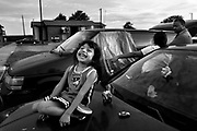 83777 --- Abisag Morales, 4, plays with her toys on the hood of an abandoned car while Pastor Rock talks with her mother Maria Palma as they try to find a solution to fix her broken down van at Sugar Hill on Wednesday July 4, 2007..Pastor Rock has spent the past three years fighting race, poverty  and violence at Sugar Hill, the poorest of the poor living in public housing in Texas' richest county, Collin County. Originating in 1969, the McKinney apartment complex rose next to an old cotton field, with 100 units that would battle decades of economic annd racial isolation, squalor, criminal neglect, crack cocaine and bureaucratic equivocation supported by millions of taxpayer dollars.