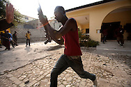 An armed security guard emerges from the campaign office of Haitian presidential candidate Jude Celestin after a crowd pelted the residence with stones. The protesters took to the streets of Port-au-Prince in support of Michel Martelly, another candidate who placed third in the previous day's announcement of preliminary election results..