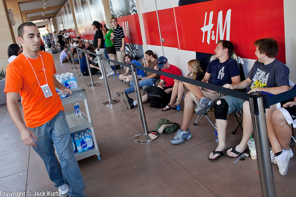 12 JUNE 2009 -- SCOTTSDALE, AZ: An Apple Store employee hands out water to people waiting to get into the store for its grand opening Friday. The outlet will be Arizona's largest Apple Store, occupying nearly 10,000 square feet in the Outdoor Lifestyle Center in the Scottsdale Quarter. The store, the fifth in the Phoenix area, uses a radically different design from other Apple Stores in some respects. Ceilings in the building are approximately 20 feet high, and lined with a 75-foot long skylight, reducing dependence on artificial lighting. Aiding the skylight is an all-glass front and rear, permitting visitors to see directly through the store. More than one thousand people lined to get into the store during the grand opening. Photo by Jack Kurtz